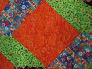 orange batik background quilted with fuschia thread in fabulous feathers
